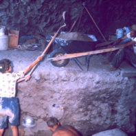 Excavators working inside the Marmes Rockshelter, shoveling soil up into a wheelbarrow, while one man works on the floor of the unit, and another waits on the surface above for the wheelbarrow to be filled; August 1962.