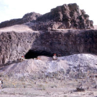 The opening of the rockshelter is viewd from the floodplain. There are several large backdirt piles with archaeologists screening dirt, while visitors approach the shelter, August 1962.
