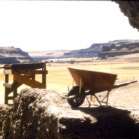 The view from inside the rockshelter shows a wheelbarrow and a screen. In the background, the view is south towards the confluence of the Palouse and Snake Rivers, July 1962