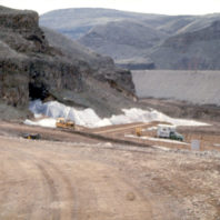 The area directly in front of the rockshelter is draped in plastic sheeting while heavy equipment levels the surface of the floodplain. The coffer dam is seen in the background rising above the floodplain, February 1969.