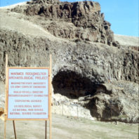 This view of the entrance to Marmes Rockshelter from the floodplain shows the informational sign.; The sign reads Marmes Shelter Archaeological Project, Washington State University, U.S. Army Corps of Engineers, Roald Fryxell, Director, Richard D. Daugherty, Co-Director, Cooperating Agencies U.S. Geological Survey, U.S. National Park Service, National Science Foundation.