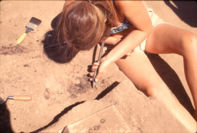 Tina Seeman excavating the burned basketry fragment with pick and CO2, August 1969