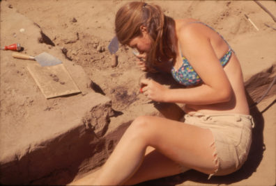 Another view of Tina Seeman excavating the basketry fragment with pick and CO2, August 1969
