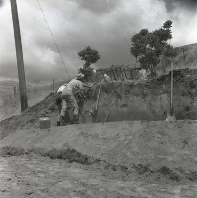 Excavators making the Initial cut in the south face of bank, Area A, 1967