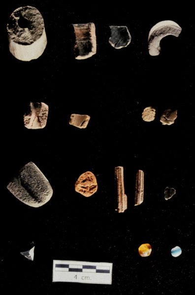 Pipes, clay, shaft abrader, faceted stone, minerals, pigments, and trade beads. A. 15-01A Unfinished pipe blank; B., C. 15-02A Pipe fragments; D. 19-04A Clay fragments; E. 18-01A Shaft abraders; F. 29-01A Red and yellow ochre; G. 29-02A Columnar red clay formation; H. 29-03A Mica; I. 17-01A Stone fragments with flat ground planes; J. 33-01A Glass trade beads, variety 1; K. 33-01B Glass trade beads, variety 2 (Source: Nakonechny 1998:Figure 84).