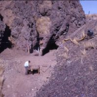 View of Squirt Cave 1964, showing the openings to the cave in the background on the left, and excavator screening dirt in the foreground, and the railroad embankment on the right