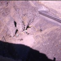 A view of Squirt Cave showing the cave openings and the railroad tracks between the cave and the river, 1964