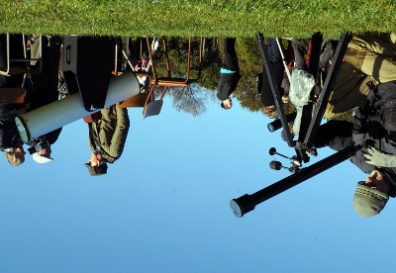 An upside down photo of people looking through telescopes