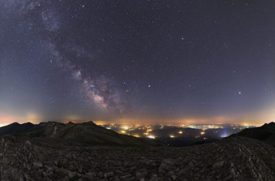 a picture of the night sky from on top of a hill with a city in the background