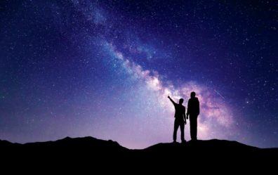 two people in front of a space background with one pointing towards the sky
