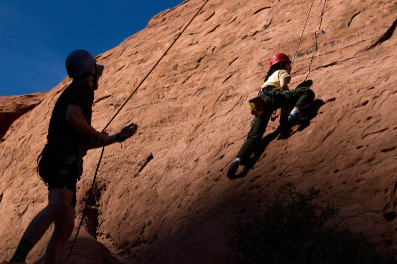 Two people rock climbing, a male is belaying while a female is climbing.