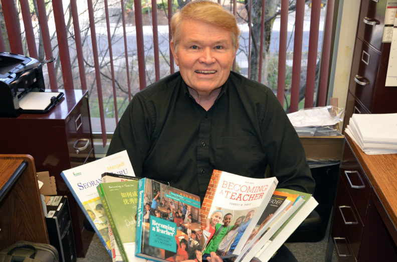 Forrest Parkay holding different editions of his book Becoming a Teacher.