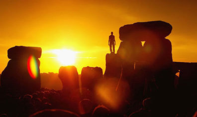 A photo of the sunset at Stonehenge with a human on one of the stones