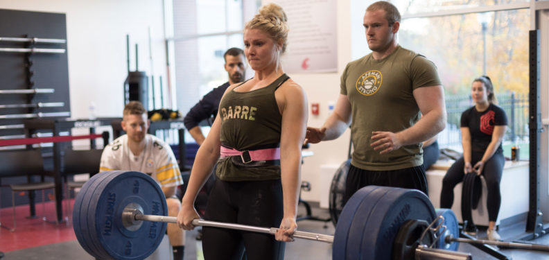 A girl lifting weights in a weight room while being spotted with a crowd of people watching