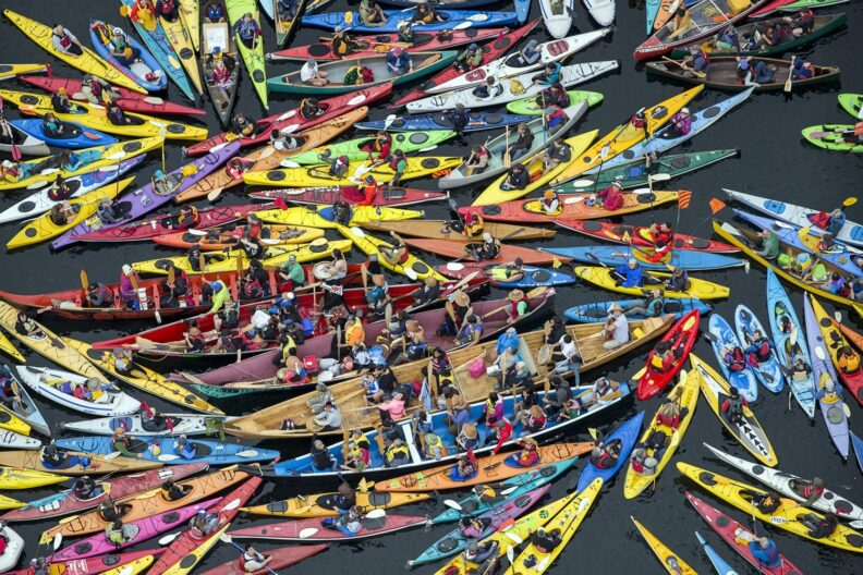 The image emphasizes the power in numbers and also the colorful and compelling nature of kayaktivism.