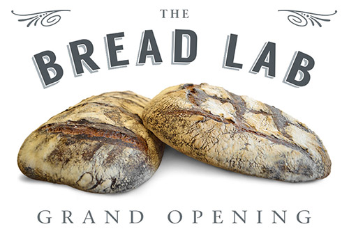 Loaves of bread with text that reads the bread lab grand opening