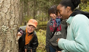 Carris, left, shows students the fruiting body of a Fomitopsis pinicola fungus growing on a tree. Photo by Bob Hubner.