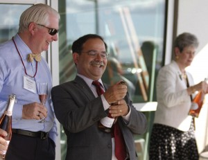 Provost Dan Bernardo, center, pops a celebratory cork with WSU Regent Mike Worthy. At right is Regent Lura Powell.