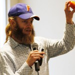 "Spencer Marshall, a graduate student in Crop and Soil Sciences, holds up an imported grocery-store tomato infected with spotted wilt virus during his presentation at the ""Science at IAREC"" expo."
