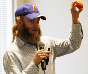 "Spencer Marshall, a graduate student in Plant Pathology, holds up an imported grocery-store tomato infected with spotted wilt virus during his presentation at the ""Science at IAREC"" expo."