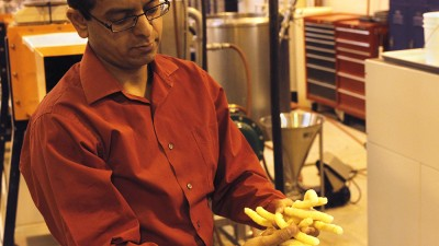 WSU professor Girish Ganjyal holds the snack puffs he and his students made with added carrot pomace.