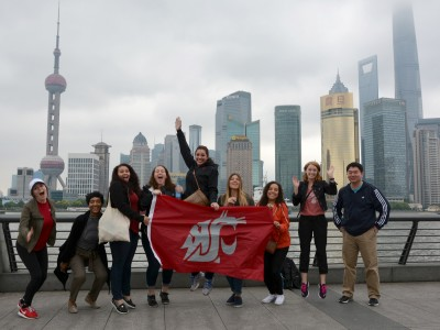 Students show their Coug flag on Shanghai's famous Bund waterfront, with views of Pudong's skyscrapers. From left are Yeseily Pruneda, Tatiana Sweat, Nikki Norman, Ariana Paynter, Katie Rae, Alison DePhillips, Graciela Vela, Kaitlyn Jo Engle, and Assistant Professor Ting Chi.