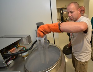 WSU researcher Brandon Hopkins lifts frozen honey bee germplasm out of the tank of liquid nitrogen, where the material is stored.