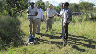 Doug Young and several Kenyan assistants observe a farmer operating the treadle pump he and his family use to irrigate his crops.