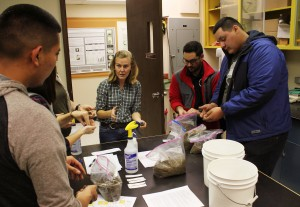 Tianna DuPont, WSU Extension tree fruit specialist, helps students with an experiment during their fall Spark tour of the WSU Tree Fruit Research and Extension Center in Wenatchee, Wash.