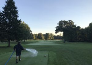 Devin Harke sprays water from a big hose on a golf course