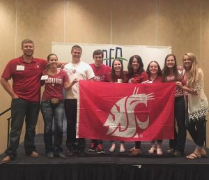 Students hold up a WSU flag in in a conference room.