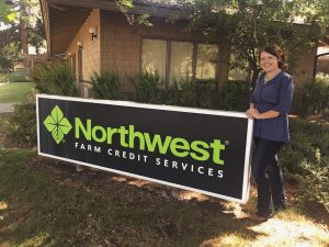 Eliana standing next to a sign for Northwest Farm Credit Services