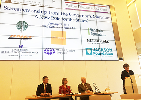 Picture of Gary Locke, Christine Gregoire and Slade Gorton, with a forum speaker, in front of a large screen showing host organizations.