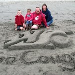 Future Cougs Wesley and Tessa Hausken with Dad, Eric ('01, Ag. Technol. & Prod. Mgmt.), and Mom, Sara ('03, Human Dev., '07, Ed.), enjoy a day at the beach, where Eric created sand art honoring his alma mater.