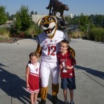 Tessa and Wesley Hausken pose with the furry version of WSU mascot Butch as the bronze incarnation looks on.