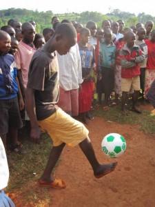 A student kicking a soccer ball.