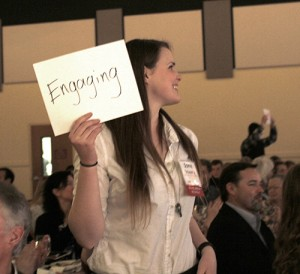 "Sophie Trombetta holds a piece of paper with the word ""engaging"" on it."