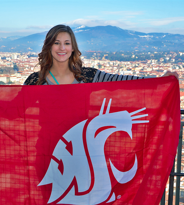 A student holding a WSU flag with a city and mountain behind her.