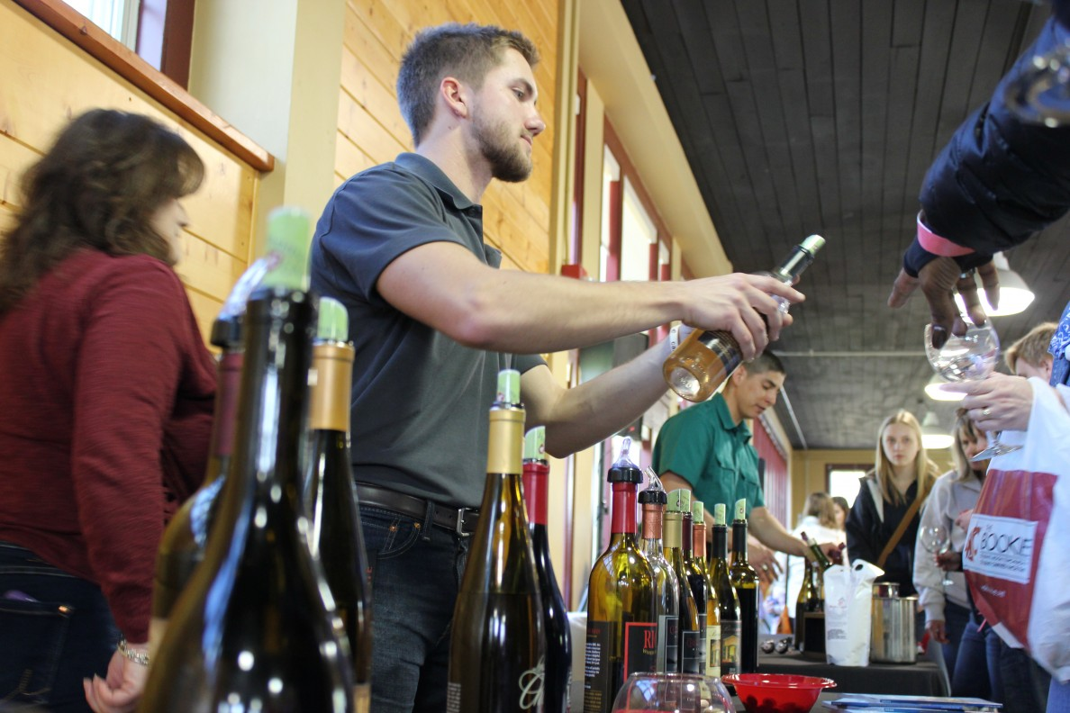 Two students pouring wine at a wine tasting event