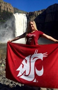 Janelle Thomas holding the WSU flag in front of a waterfall