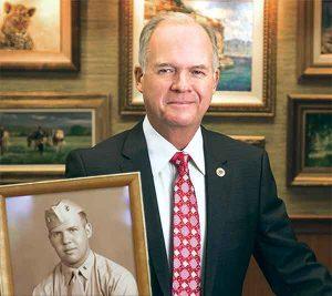 Gary Schneidmiller with a portrait of his father, Manuel Schneidmiller, in uniform.