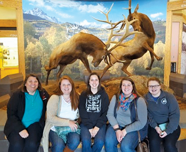 Candis Carraway, Mariah Julson, Megan Blyzka, Reni Lucido, and Shania Simons in front of a museum diorama of two elks fighting.