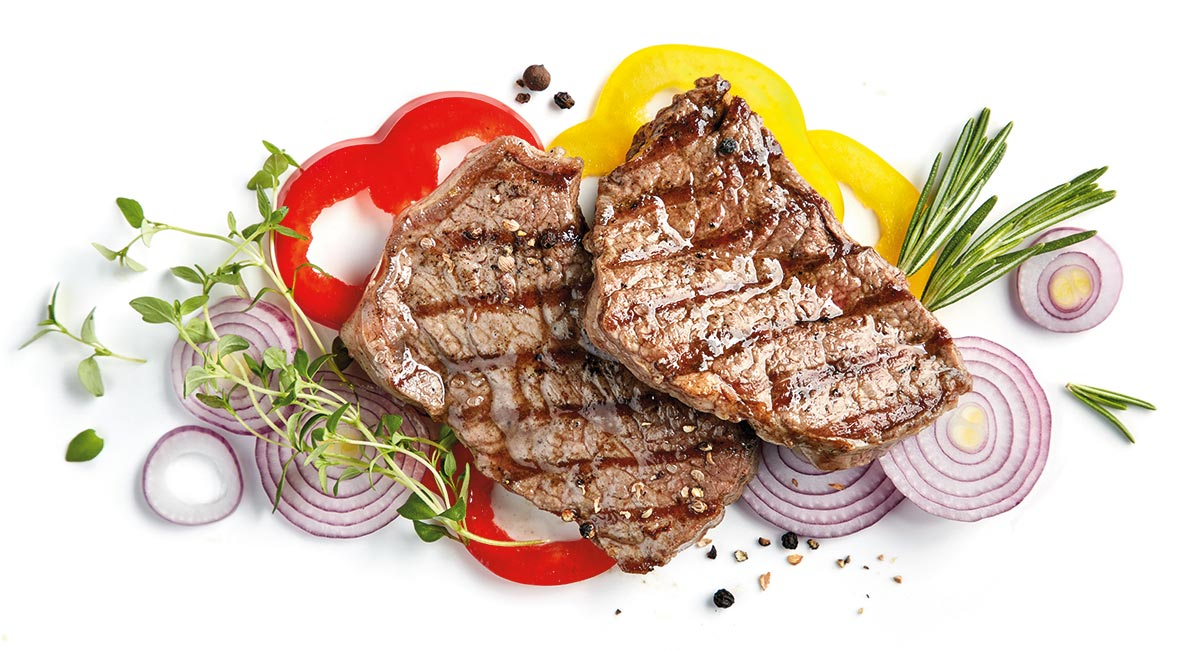 Two juicy steaks with bell peppers, red onions, rosemary and thyme.