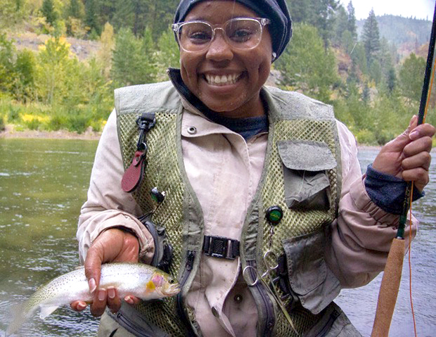 Tomyia Wallace holder her catch and fly fishing rod.