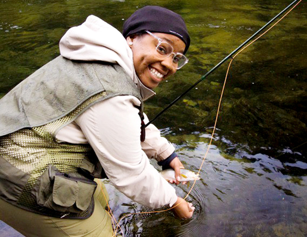 Tomyia Wallace, smiling, holding her fish and fly fishing rod bent over the stream.