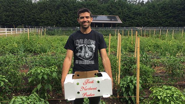 Man holding a box of produce on a farm