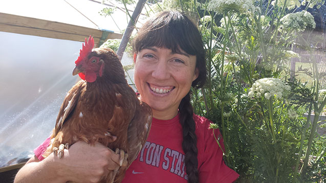 A woman holding a chicken