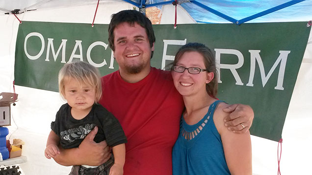 A man, woman, and child in front of a sign that read Omache Farm