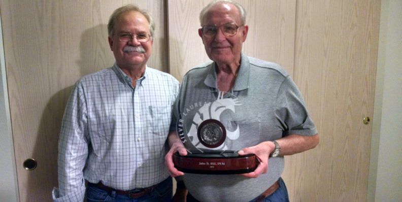John Hill holding his silver laureate statue with Bryan Slinker