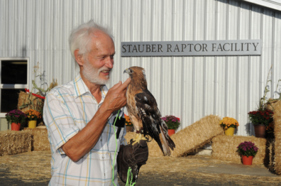 Erik Stauber wtih a raptor in front of the Stauber Raptor Facility